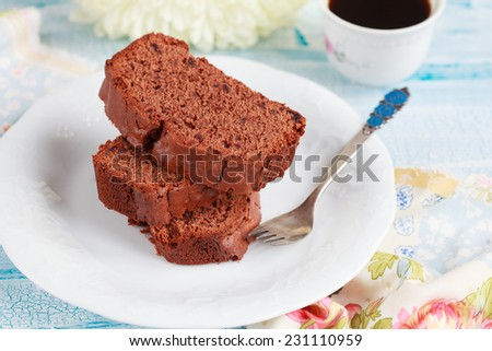 Slices of homemade chocolate cake with figs on white plate and a flower and cup of coffee  on wooden table, selective focus