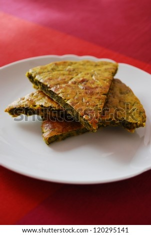 Slices of homemade vegetarian chickpeas cake with herbs in a white dish - stock photo