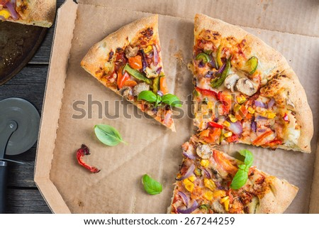 slices of homemade vegetarian pizza in box from above - stock photo