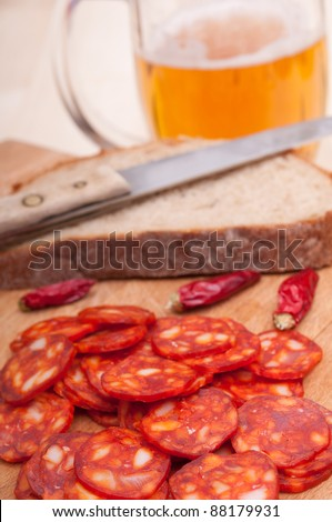 Slices of Hungarian Sausage on Chopping Board With Chilies, Bread and Glass of Beer