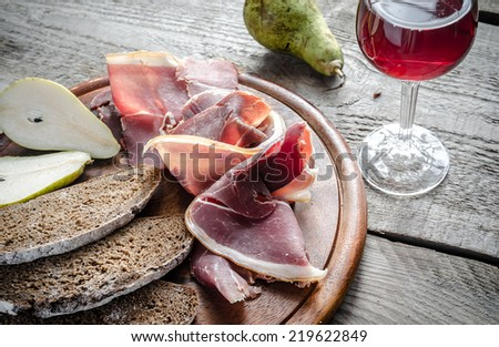 Slices of italian ham with on the wooden board - stock photo