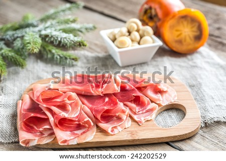 Slices of jamon on the wooden board - stock photo