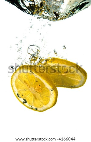 Slices of lemon plunging into clean fresh cold water - stock photo