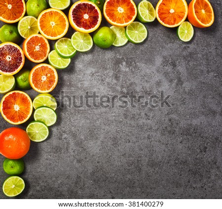 Slices of lime and blood orange fruits on grey stone background. Healthy eating and dieting concept. Copy space. Top view - stock photo