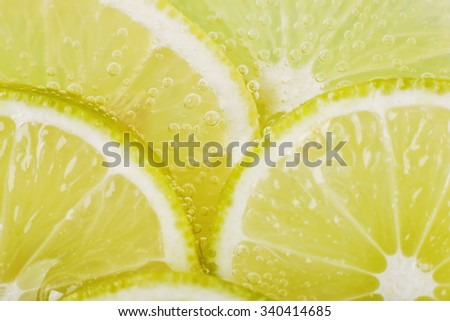 Slices of lime in soda water. Lime Cocktail. The liquid drink. Bubbles of carbon dioxide. The background texture. Tropical citrus fruit. Macro Lime, macro lemon. Ingredient. - stock photo