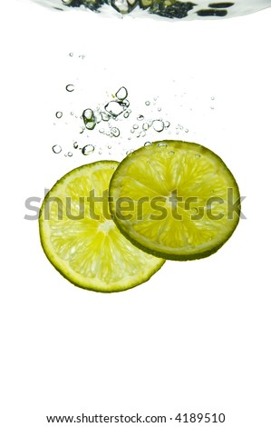 Slices of lime plunged into refreshing water - stock photo