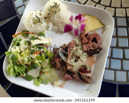 Slices of Meat Steak, White Rice, Pineapple slice, flower, and Salad with dressing on square white plate on a table. - stock photo