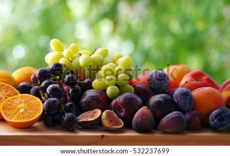Slices of orange and fig fruits, grapes and plums on table