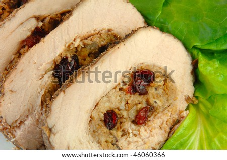Slices of pork roast stuffed with apple and cranberry stuffing on a bed of lettuce.
