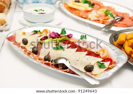 Slices of prosciutto, cheese and kulen sausage sorted on silver plate