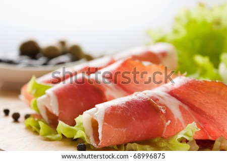 Slices of prosciutto rolled up and arranged on a lettuce leaf. Shallow depth of field. - stock photo