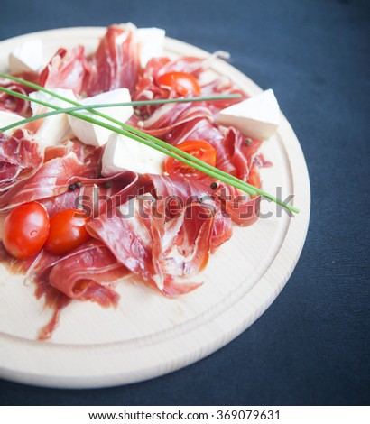 slices of prosciutto with mixed cherry tomatoes and cheese brie on wooden cutting board over the dark grey background. Flat lay concept