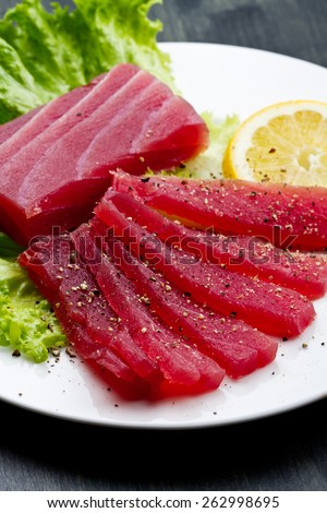 Slices of raw bluefin tuna  sashimi on white dish on wood background - stock photo