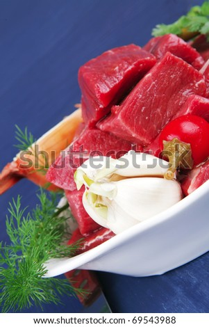slices of raw fresh beef meat fillet in a white bowls with garlic and red peppers serving on blue table with cutlery