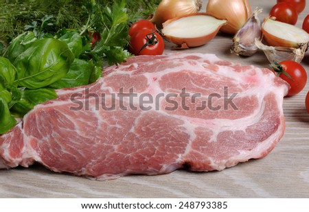 Slices of raw pork steak with greens and vegetables