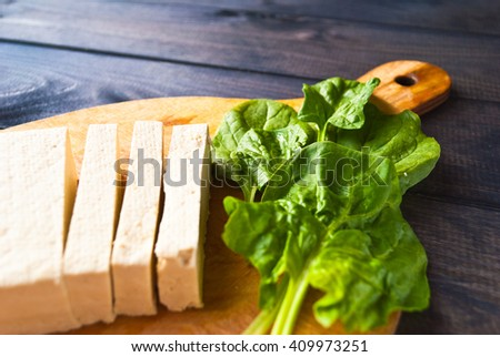 Slices of raw tofu and green leaves of fresh spinach on cutting board. Vegetarian cuisine - stock photo