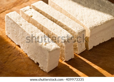 Slices of raw tofu on beige cutting board in sunlight - stock photo