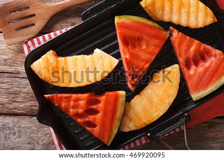Slices of ripe watermelon and melon in a pan grill close-up on the table. Horizontal view from above