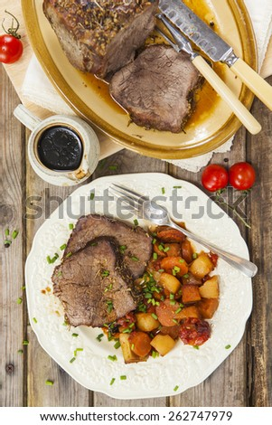 Slices of roast beef garnished with vegetables served on vintage plate and jug of sauce on rustic wooden table with roast beef joint on oval plate and carving set - stock photo
