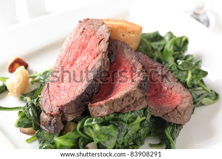 Slices of roast beef with sauteed spinach - stock photo