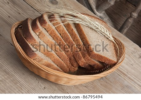 slices of rye bread and ears of corn in the basket - stock photo