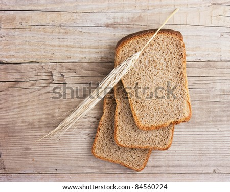 slices of rye bread and ears of corn on the wooden table - stock photo