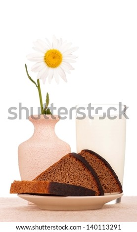 Slices of rye bread with milk on a burlap over white background - stock photo