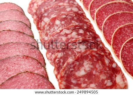 Slices of salami on white background - stock photo