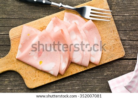 Slices of Sausage Mortadella and fork on cutting board - stock photo