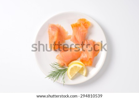 slices of smoked salmon on white plate - stock photo