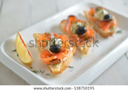 slices of smoked salmon with olives and butter on fried (soft focus)