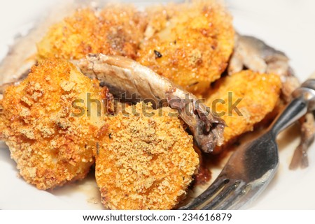 slices of smoked sprats canning and roasted potatoes - stock photo