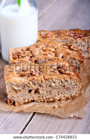 Slices of snack whole meal cake with apples walnut and bottle of milk