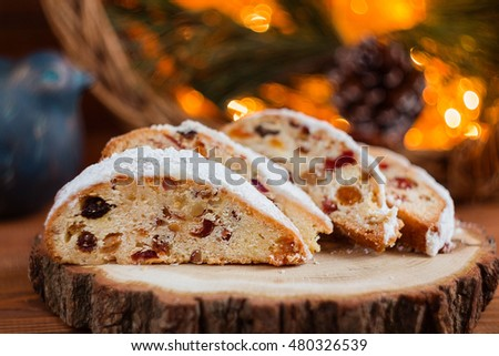 Slices of stollen on festive rustic wooden background with cchristmas light bokeh. Shallow focus