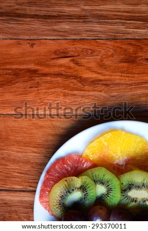 Slices of strawberries, grapes, pinapple, kiwi, orange and grapefruit on a plate. Fruit platter. - stock photo