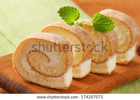 Slices of sweet cream roll on a cutting board - stock photo