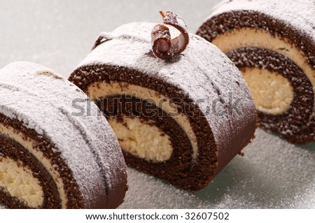 Slices of swiss roll chocolate cake on frosted glass plate
