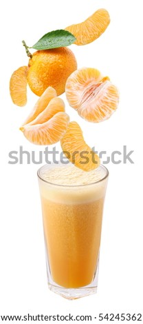 Slices of tangerine falling into a glass of fresh juice - stock photo