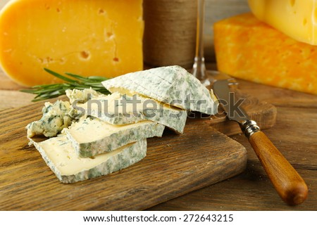 Slices of tasty blue cheese on cutting board close up
