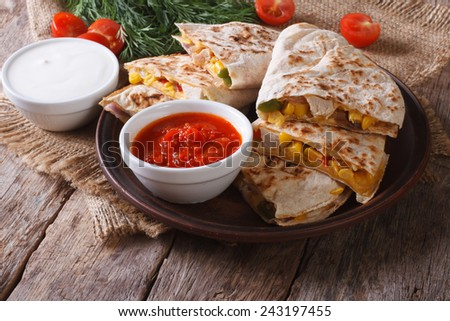 Slices of tasty Mexican quesadilla on a plate and sauces closeup. horizontal  - stock photo