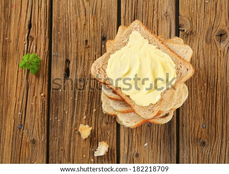 Slices of toast bread  with butter on wooden table - stock photo