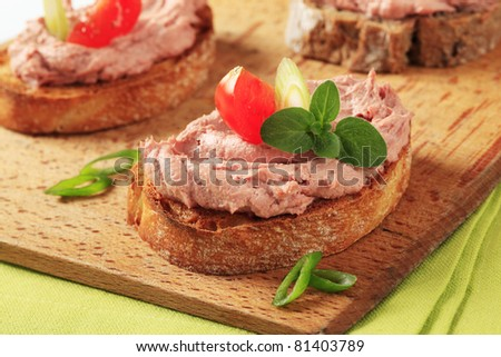 Slices of toasted bread with delicious liver pate  - stock photo