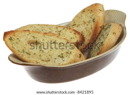 Slices of toasted garlic and herb bread in an earthenware dish - stock photo