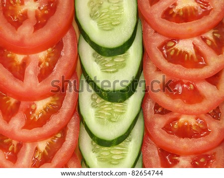 Slices of tomato and cucumber arranged in a row suitable as background. - stock photo