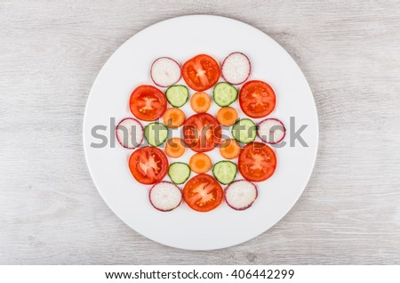 Slices of tomatoes, radishes, carrots and cucumbers in white glass plate on wooden table. Top view - stock photo