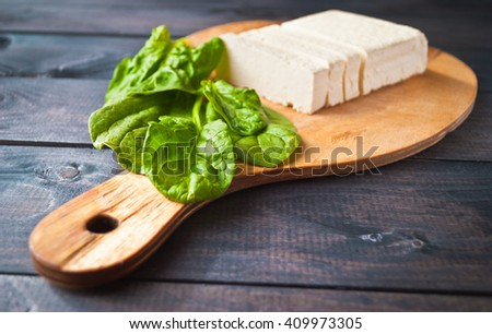 Slices of uncooked tofu and green leaves of fresh spinach on rustic cutting board - stock photo