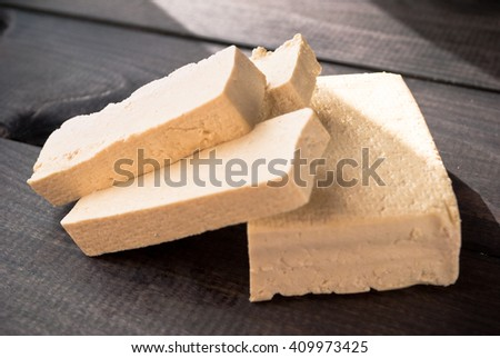Slices of uncooked tofu on wooden background in sunlight. Ingredient for vegetarian cuisine - stock photo