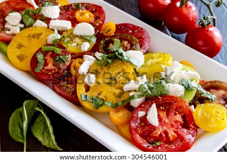 Slices of vine ripe heirloom tomato varieties with fresh basil, salt, pepper, olive oil and fresh herbs sitting on square white plate