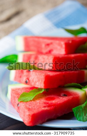 Slices of watermelon with mint leaves on blue ceramic plate