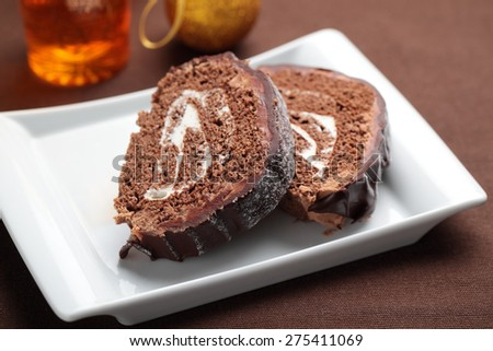 Slices of Yule log cake topped with chocolate on a Christmas table - stock photo